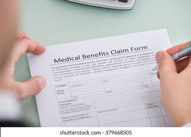Close-up Of Person Hand Over Medical Benefits Claim Form