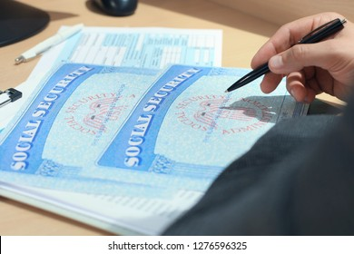 Closeup of person hand with pen filling Social Security blank.