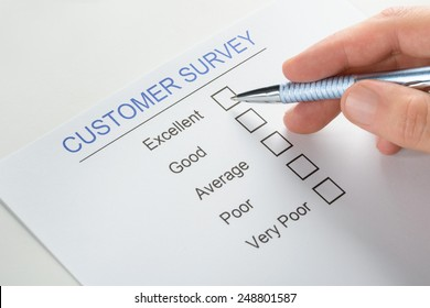 Close-up Of Person Hand With Pen Over Blank Customer Survey Form