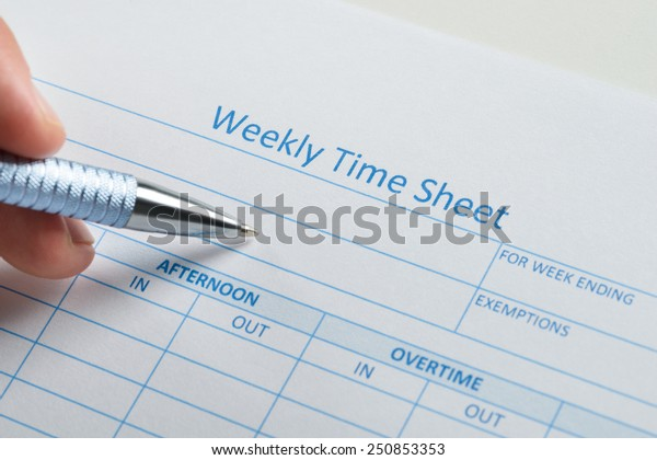 Close-up Of Person Hand With Pen Over Blank Weekly Time Sheet