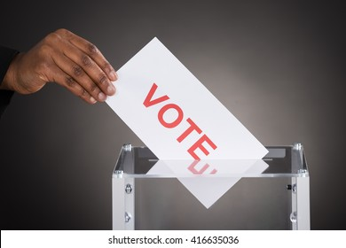 Close-up Of A Person Hand Putting Vote In A Ballot Box Against Gray Background