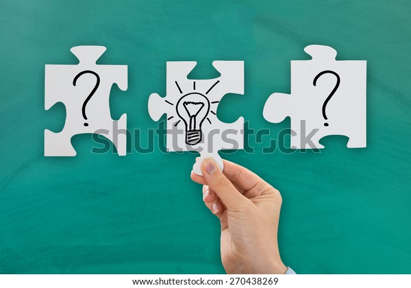 Close-up Of Person Hand With Puzzle Showing Bulb And Question Mark Symbol