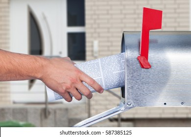 Close-up Of A Person Hand Removing Newspaper From Mailbox Outside The House