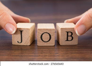 Close-up Of Person Hand Saving Wood Blocks With The Word Job