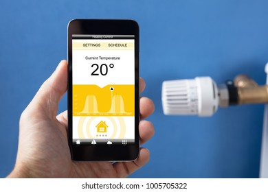 Close-up Of Person Hand Setting Temperature Of Thermostat Using Mobilephone At Home