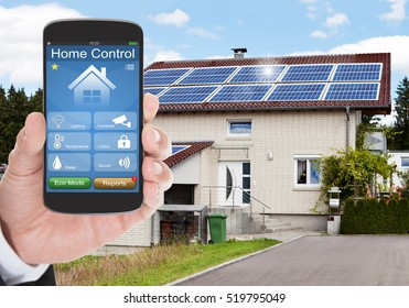 Close-up Of Person Hand Using Home Control System On Mobilephone Outside The House