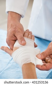 Close-up Of Person Hand Wrapping Bandage To Patient