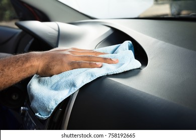 Close-up Of Person Hands Cleaning Car Interior With Blue Cloth