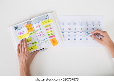 Close-up Of Person Hands Highlighting Date On Calendar With Diary At Desk