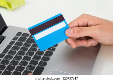 Close-up Of Person Hands Holding Credit Card Over Laptop Keypad
