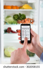 Close-up Of Person Hands Making Shopping List On Mobile Phone Display Connected To Refrigerator