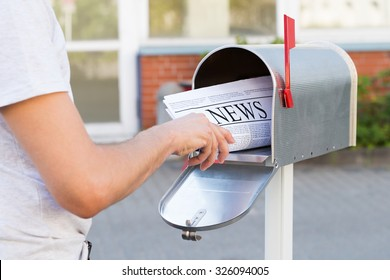 Close-up Of Person Hands Opening His Mailbox To Remove Newspaper