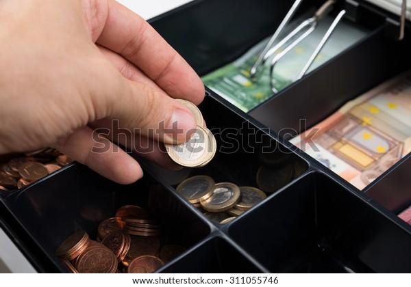 Nahaufnahme von Händen von Personen, die Münzen im Kassenregister eintragen