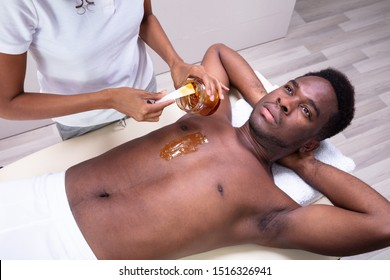 Close-up Of Person Hands Waxing Man's Chest With Wax Strip