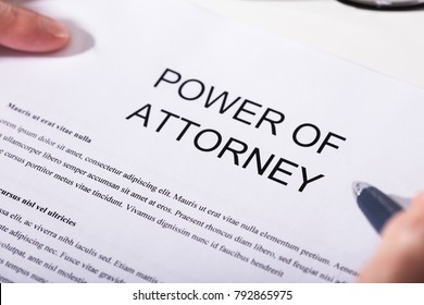 Close-up Of A Person Holding Pen Over Power Of Attorney Form