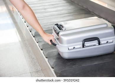 Close-up of a person holding suitcase on conveyor belt.
