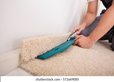 Close-up Of A Person Installing Floor Carpet With Cutter
