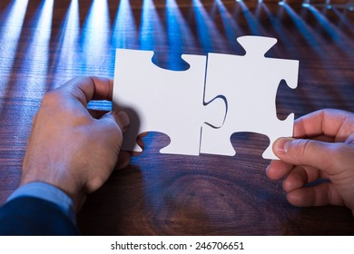 Close-up Of A Person Joining Two Jigsaw Pieces On Desk