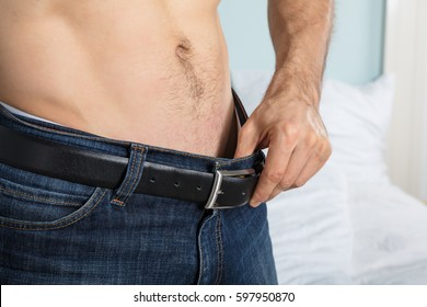 Close-up Of A Person Looking Inside His Jeans At Home