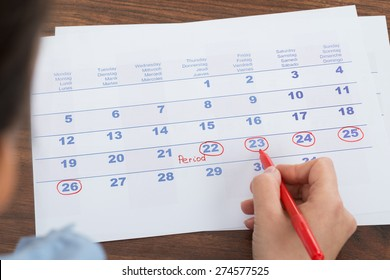 Close-up Of Person Marking Menses Date On Calendar
