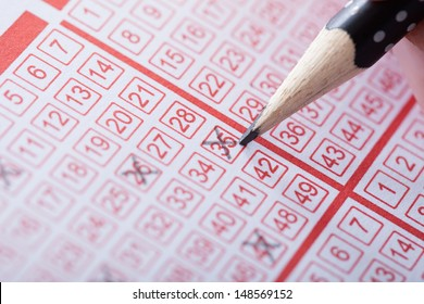 Close-up Of A Person Marking Number On Lottery Ticket With Pencil