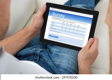 Close-up Of Person On Sofa With Digital Tablet Showing Survey Form