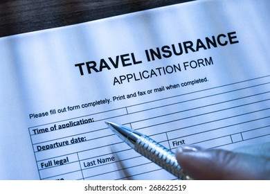 Close-up Of A Person With Pen Filling Travel Insurance Application Form