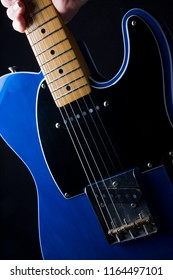 close-up of a person picking up an electric guitar.