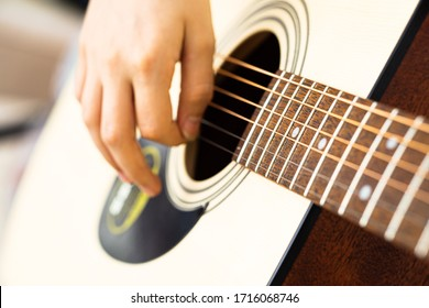 close-up person playing guitar image