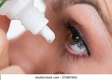 Close-up Of Person Pouring Drops In Eyes With Eyedropper