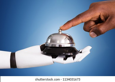 Close-up Of A Person Ringing Service Bell Hold By Robot Against Blue Background