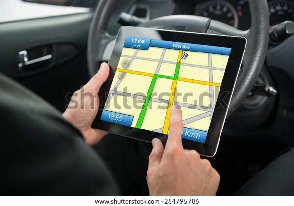 Close-up Of A Person Sitting In A Car Using Gps Service On Digital Tablet