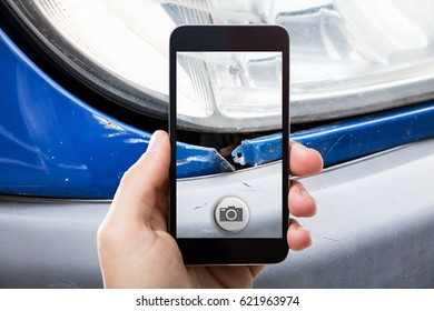 Close-up Of A Person Taking Picture Of A Damaged Car On Mobile Phone