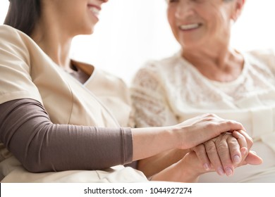 Close-up of person touching hand of senior woman. Caregiver in the nursing home