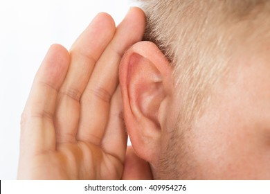 Close-up Of Person Trying To Hear With Hand Over Ear