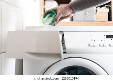 close-up of person using dosing aid to pout laundry detergent powder into washing machine