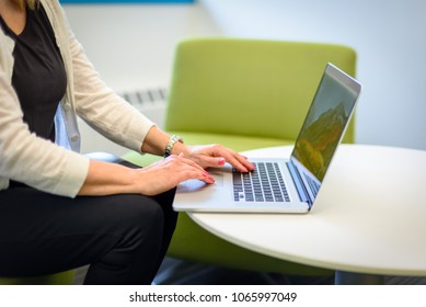 closeup of person using a laptop in modern office