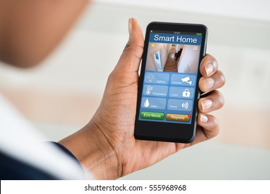 Close-up Of Person Using Smart Home System On Mobilephone At White Desk