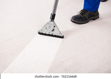 Close-up Of A Person Using Vacuum Cleaner For Cleaning Carpet At Home