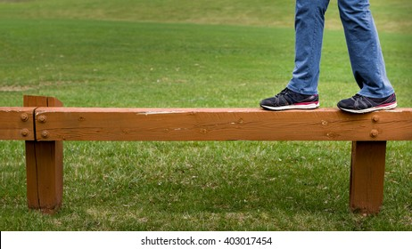 Closeup of person walking on wooden guard rail in park