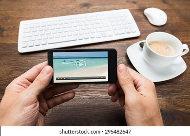 Close-up Of Person Watching Video On Mobile Phone With Cup Of Tea At Desk