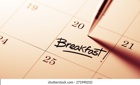 Closeup of a personal agenda setting an important date written with pen. The words Breakfast written on a white notebook to remind you an important appointment.
