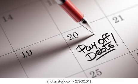 Closeup of a personal agenda setting an important date written with pen. The words Pay off debts written on a white notebook to remind you an important appointment.