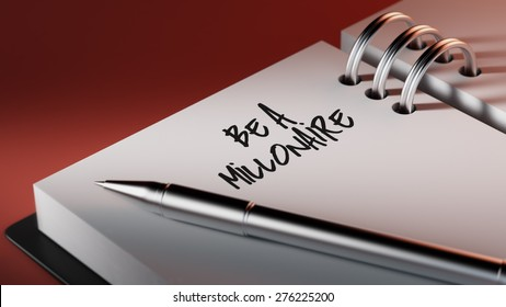 Closeup of a personal agenda setting an important date writing with pen. The words Be a millionaire written on a white notebook to remind you an important appointment.
