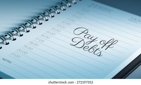 Closeup of a personal calendar setting an important date representing a time schedule. The words Pay off debts written on a white notebook to remind you an important appointment.