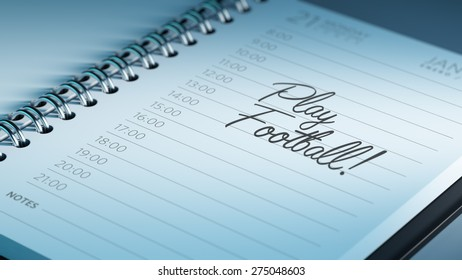 Closeup of a personal calendar setting an important date representing a time schedule. The words Play Football written on a white notebook to remind you an important appointment.
