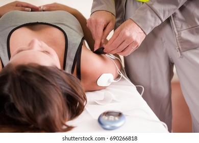 Close-up of a personal trainer hand putting an electrostimulator electrodes in the arm and shoulder of a female deportist, lying on her back