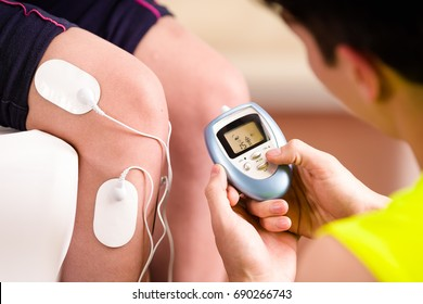 Close-up of a personal trainer holding with one hand the electric machine and putting the electrostimulator electrodes in the leg of a female deportist, upside down on a bed