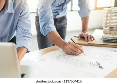 Close-up Of Person's engineer Hand Drawing Plan On Blue Print with architect equipment, Architects discussing at the table, team work and work flow construction concept.