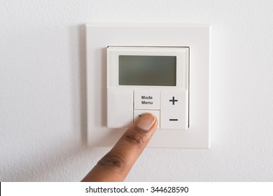 Close-up Of Person's Finger Adjusting Room Temperature On Digital Thermostat